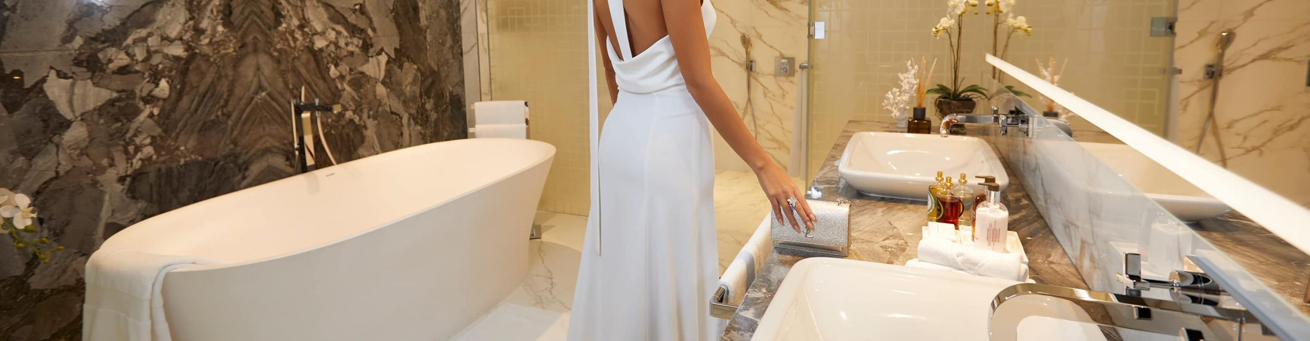 A young woman stands in her luxury bathroom