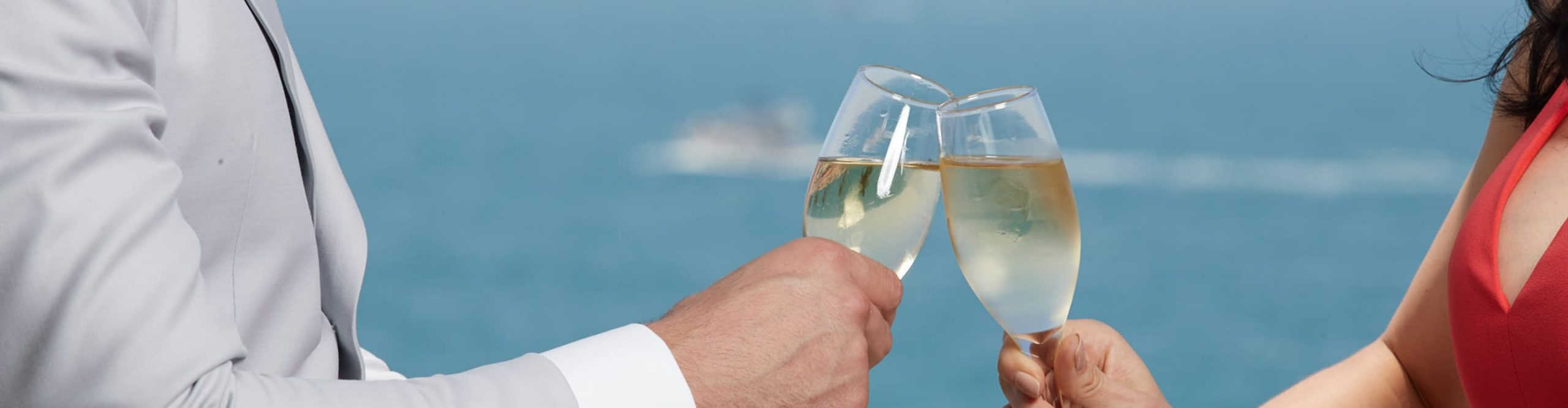 Two Champagne flutes touch in a toast