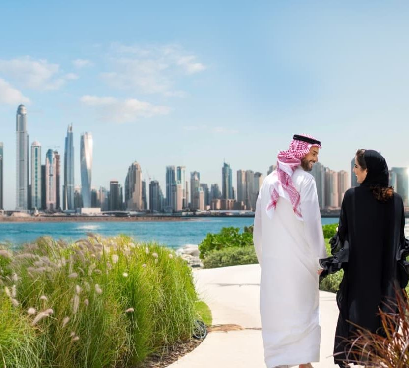 An emirati couple walk along a path in front of the Dubai skyline