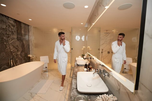 A man in the luxury bathroom of his penthouse