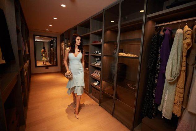 A woman strides through her walk in wardrobe in her luxury apartment