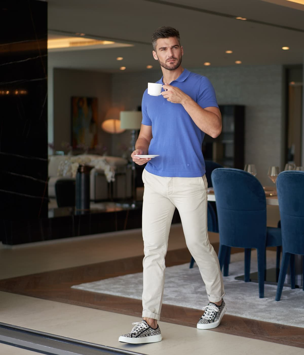 A man in a blue shirt drinks a coffee while walking