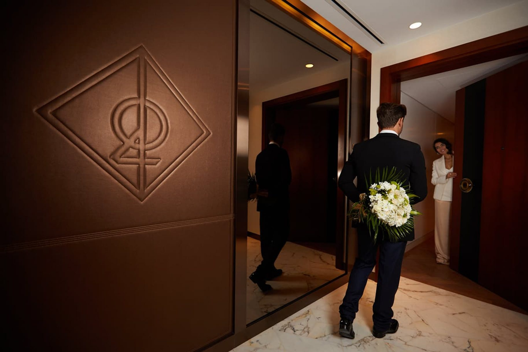 A man hides a bunch of flowers behind his back as a woman opens the door to her luxury apartment