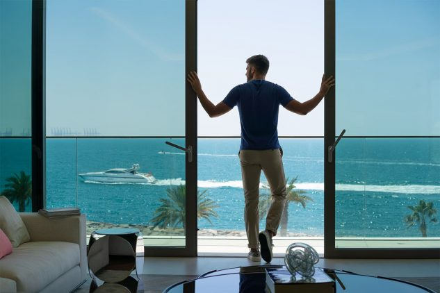 A man opens the balcony doors of a waterfront penthouse residence in Dubai
