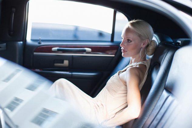 A blonde woman sits in the back of a luxury car
