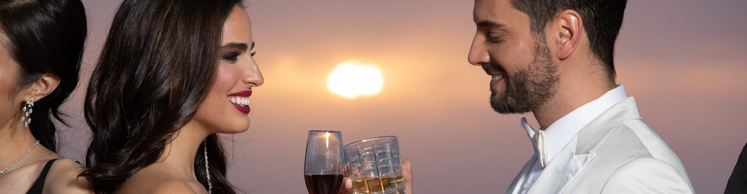 A couple share a toast at sunset
