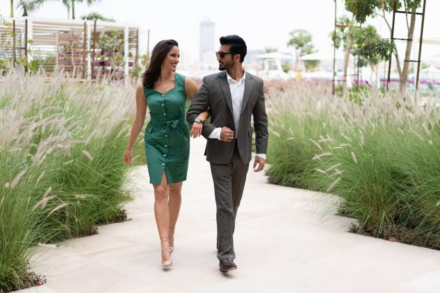 A young couple walk along a grass lined path at W Residences Palm