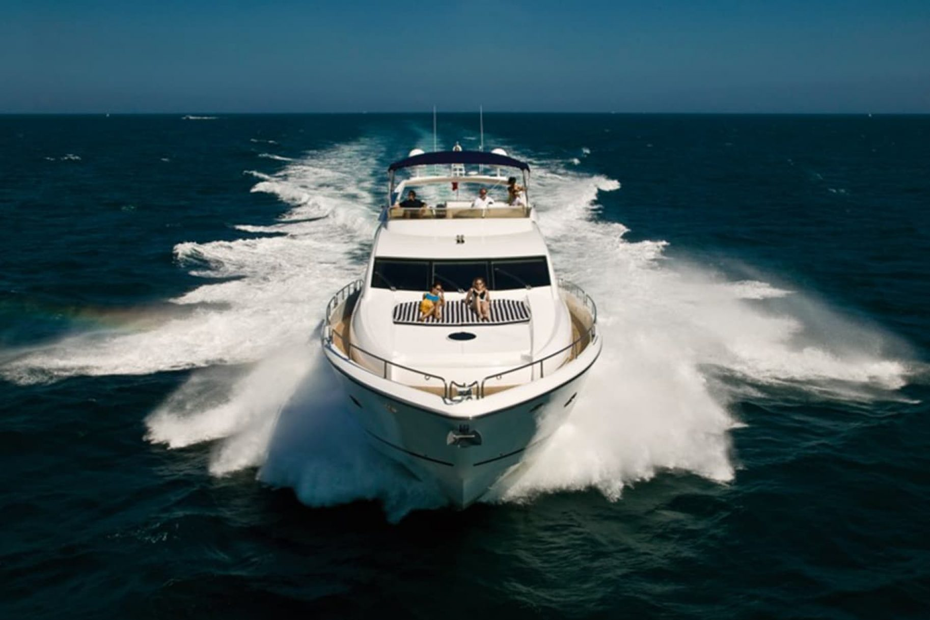 A luxury boat powers through the waves on a sunny day