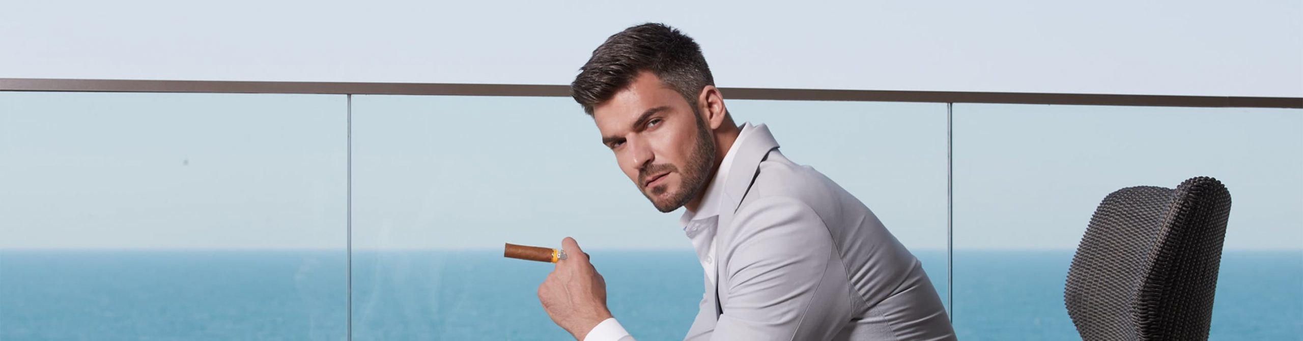 A serious man holds an unlit cigar on a waterfront apartment balcony