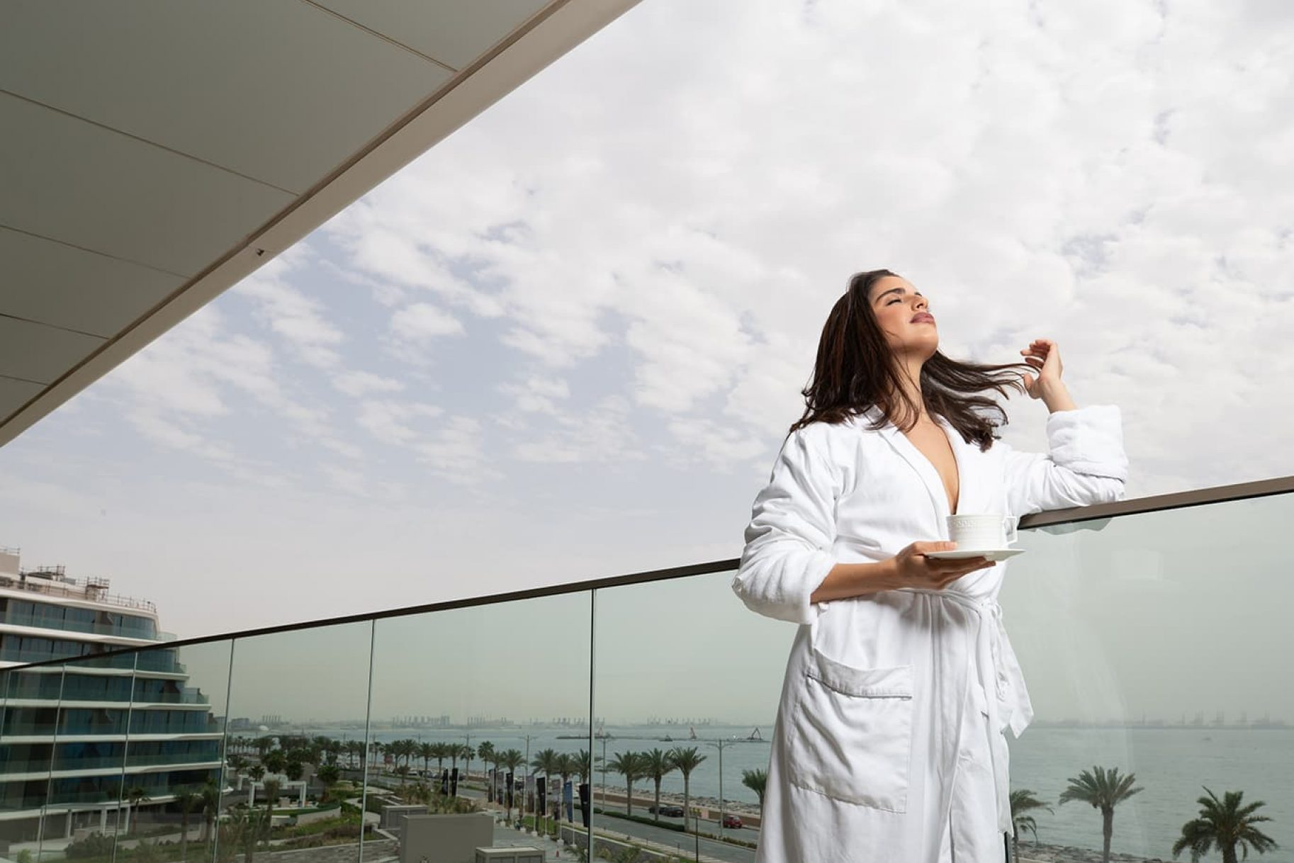 A woman in a bath robe enjoys the view from her waterfront apartment