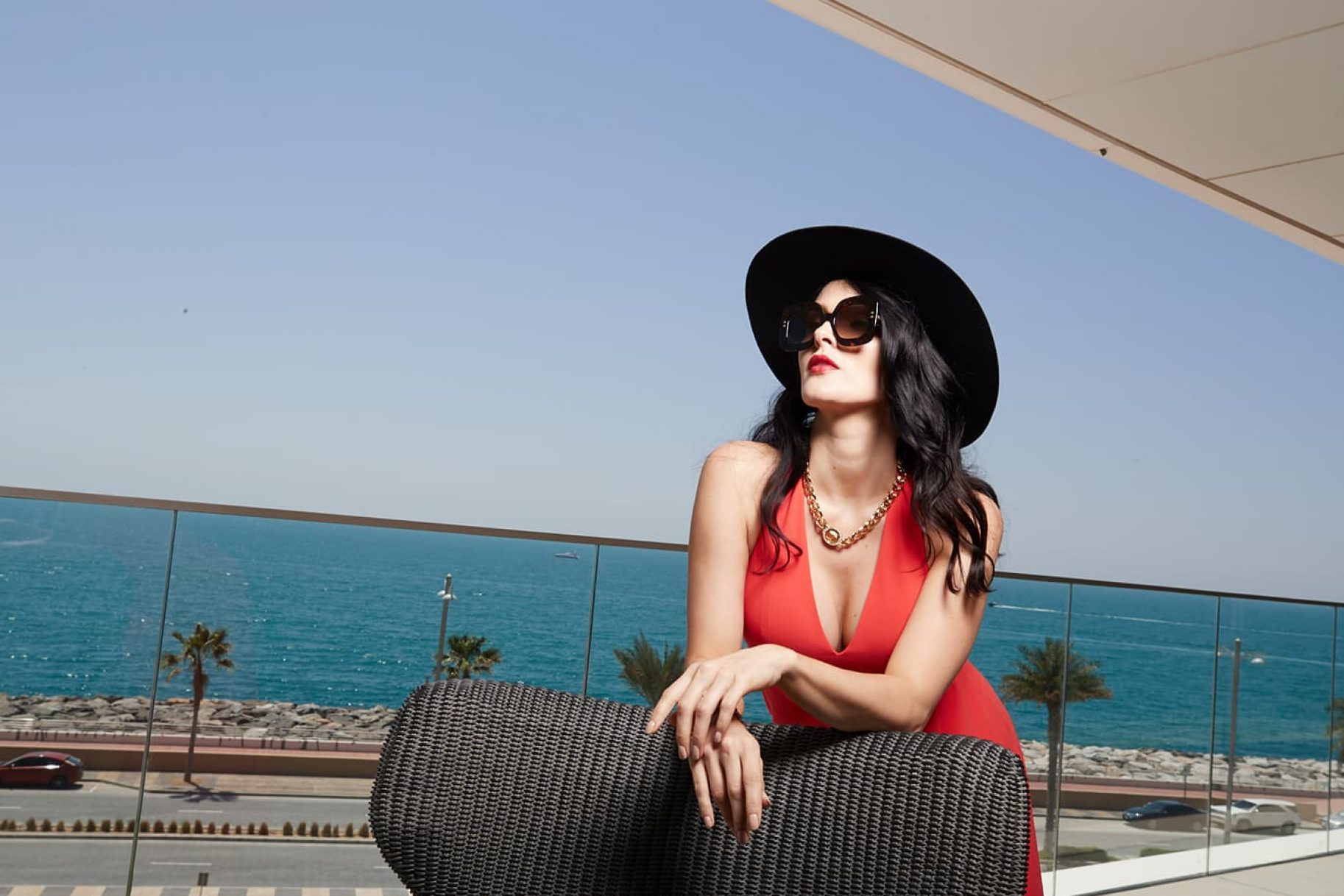 A beautiful woman in a hat sits on the balcony of a waterfront luxury property in Dubai