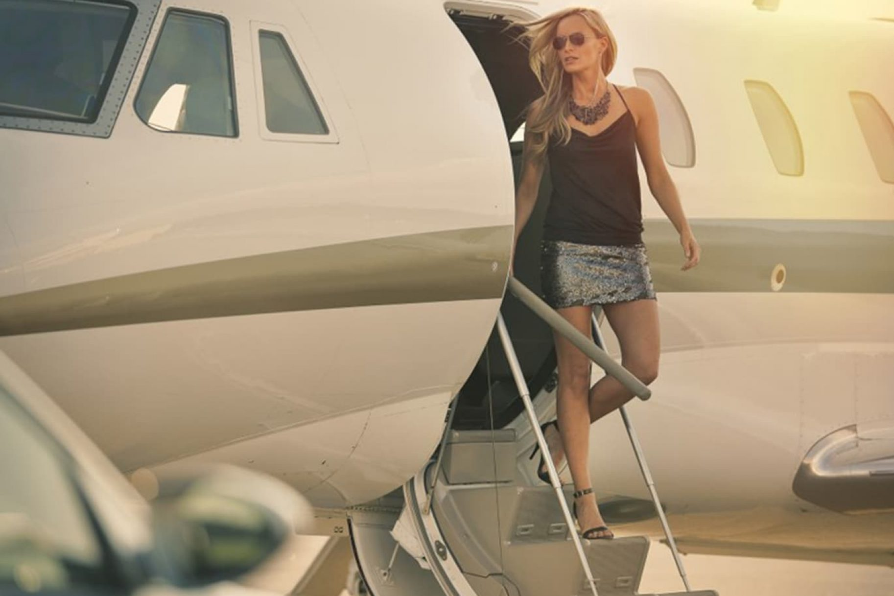 A woman steps down from a private jet at sunset