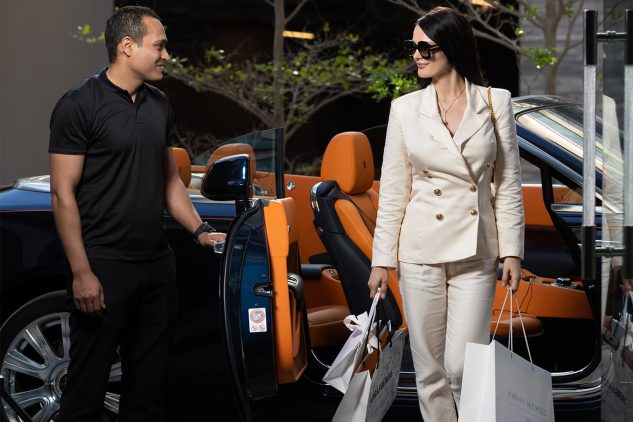 A woman steps out of a Rolls Royce with shopping bags in a scene that represents luxury