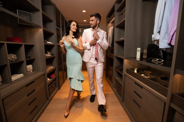 A young couple get ready to go out in their walk in wardrobe