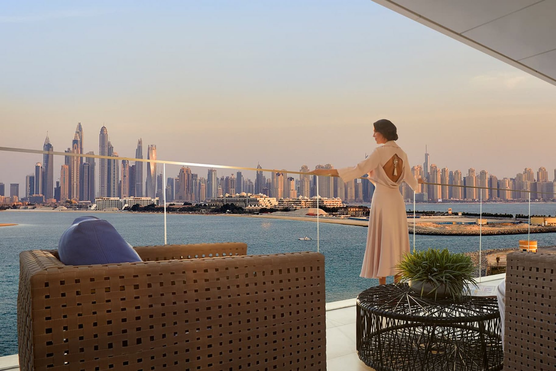 A woman looks at the Dubai skyline from the balcony of a waterfront apartment