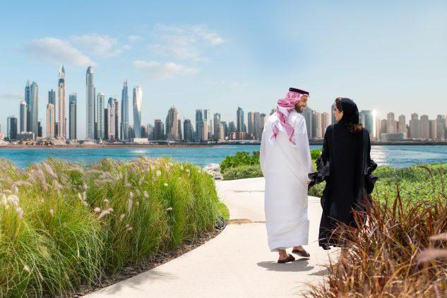 A man and woman in arabian dress walk along a path towards the Dubai skyline