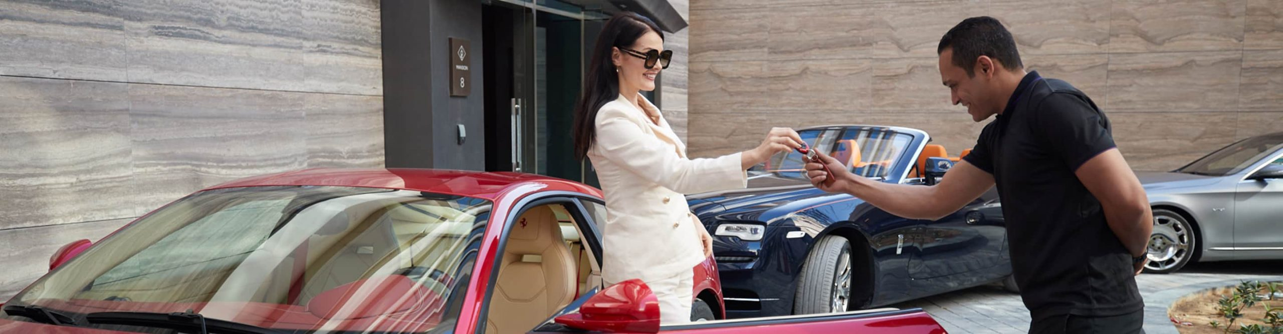A woman hands over the keys to the W Residences parking attendant