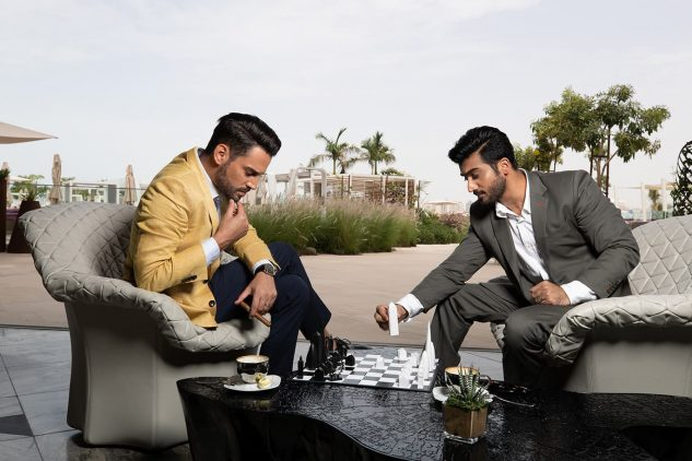 Young Emirati men enjoy a game of chess at W Residences Dubai