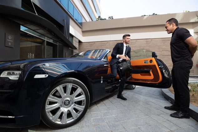 A man steps out of a Rolls Royce and is met by a concierge outside the W Residences apartments Dubai