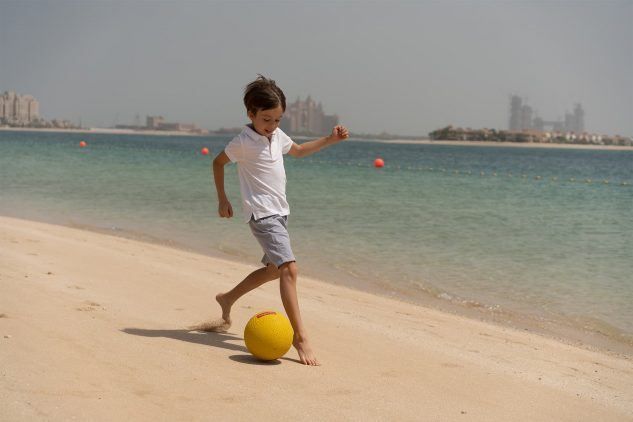 A child plays football on a beach in Dubai with the Atlantis Hotel, Palm Jumeirah in the background