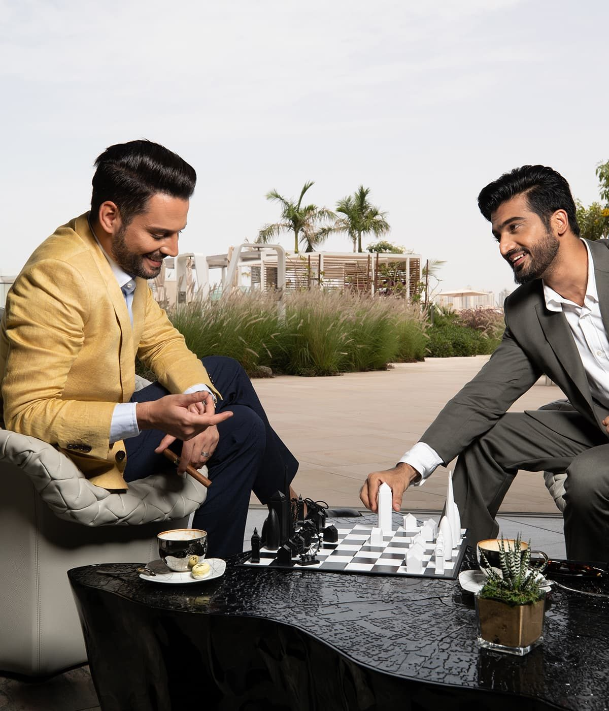 Two young men play a game of chess in the luxurious setting of W Residences club