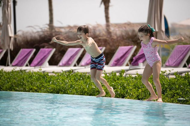 A boy and a girl jump in to a luxury pool at the W Residences apartments in Palm Jumeirah, Dubai