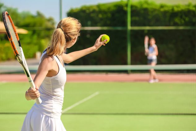 A young woman plays tennis on one of the courts at W Residences luxury apartments Dubai