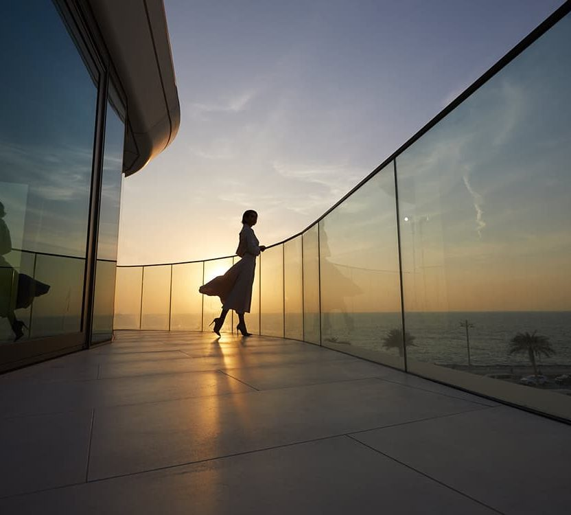A woman stands on the balcony of her waterfront apartment at sunset