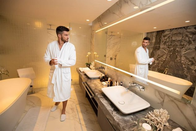 A young man looks in the mirror of his luxury bathroom